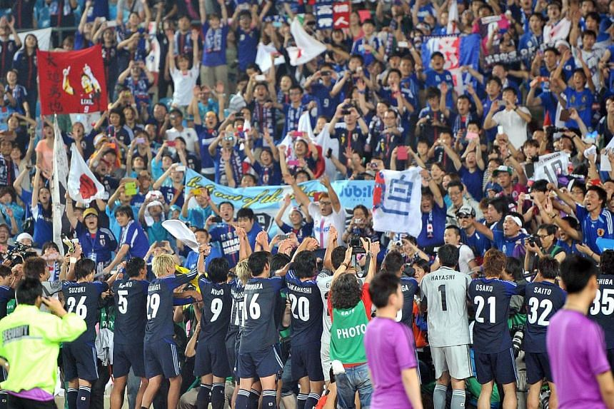 Japan's players celebrate with their supporters after winning the East Asian Cup football match in Seoul on July 28, 2013. Political banners and a military flag displayed at a football match between South Korea and Japan have dragged top government o