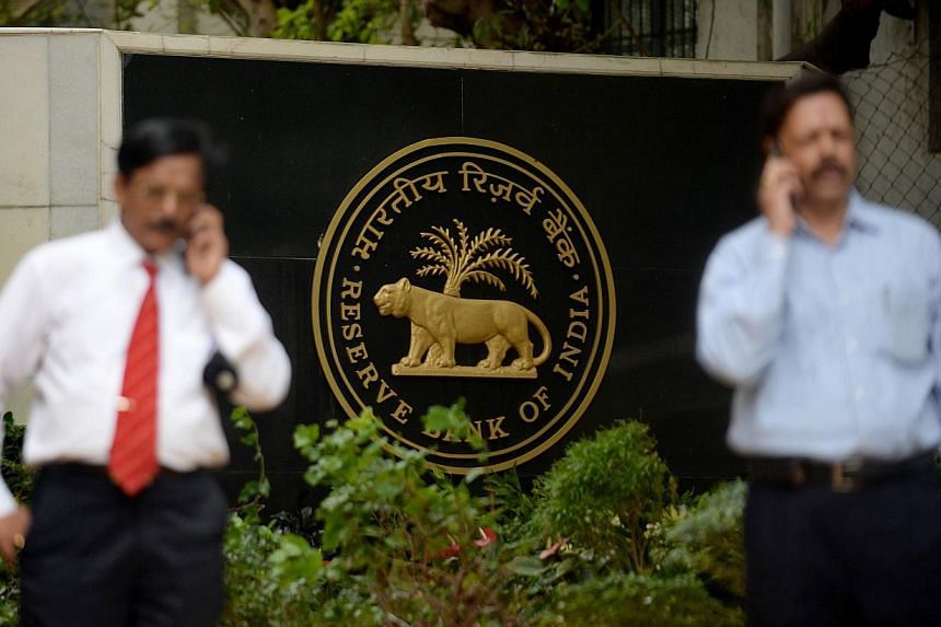 """People speak on their mobiles outside the Reserve Bank of India (RBI) headquarters in Mumbai on July 30, 2013. India's central bank governor has decided to """"move on"""" and a hunt for his successor is underway, the country's finance minister was quoted"""