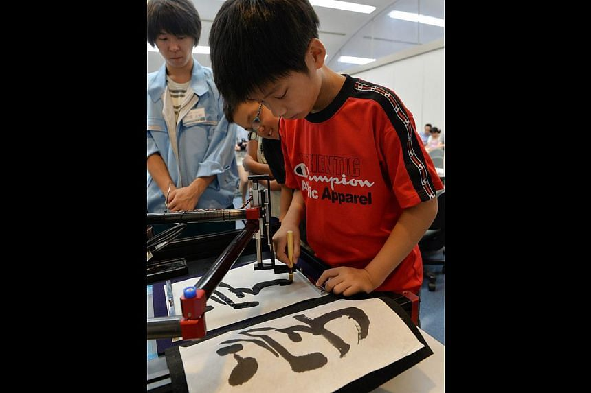 """A boy writes a Chinese letter for """"study"""" with a calligraphy robot, which mimics the exact brush strokes of a master calligrapher, at a science workshop for elementary children at Keio University in Yokohama, suburban Tokyo on July 30, 2013. -- PHOTO"""