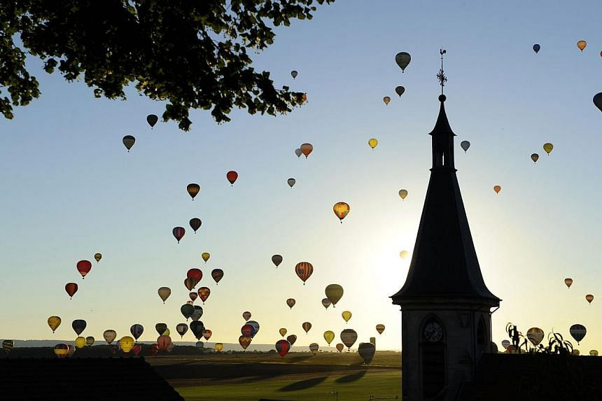Hot air balloons fly near a church over Chambley-Bussieres, eastern France, on Wednesday, July 31, 2013, at sunset, to try to set a world record with 408 balloons in the sky, as part of the yearly event Lorraine Mondial Air Ballons, an international