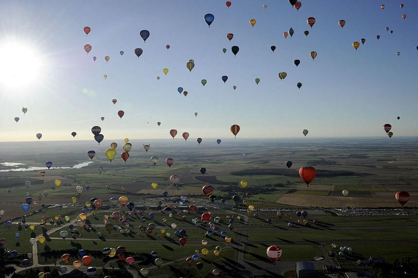 Over 400 hot air balloons take off in Chambley-Bussieres, eastern France on Wednesday, July 31, 2013, in an attempt to set a world record for collective taking-off during the event Lorraine Mondial Air Ballons, an international hot-air balloon meetin