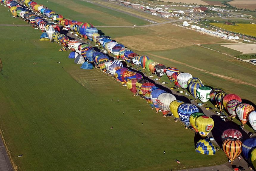 Hot air balloons prepare to take off in Chambley-Bussieres, eastern France, before the world record attempt of the biggest line with 391 balloons on Thursday, Aug 1, 2013, as part of the yearly event Lorraine Mondial Air Ballons, an international air