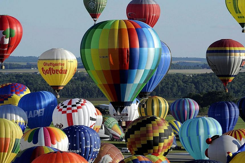 Hot air balloons take off from Chambley-Bussieres, eastern France, to try to set up a world record with 408 balloons in the sky on Wednesday, July 31, 2013, as part of the yearly event Lorraine Mondial Air Ballons, an international air-balloon meetin