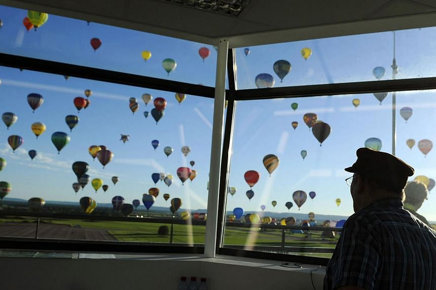 Hot air balloons are pictured from a control tower while flying over Chambley-Bussieres, eastern France, on Wednesday, July 31, 2013, to try to set a world record with 408 balloons in the sky, as part of the yearly event Lorraine Mondial Air Ballons,