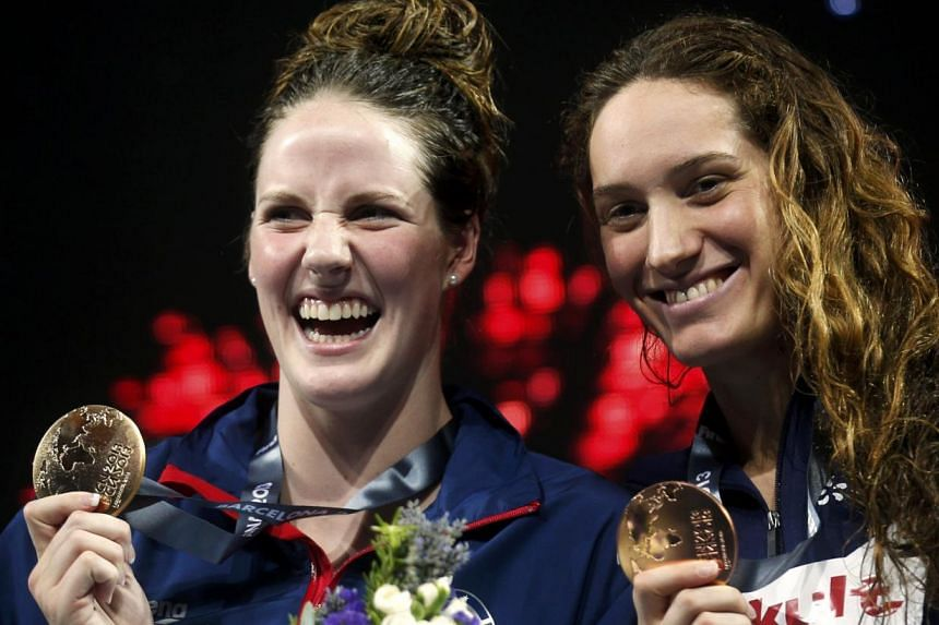 Gold medallist Missy Franklin (L) of the U.S. poses with bronze medallist Camille Muffat of France at the women's 200m freestyle victory ceremony during the World Swimming Championships at the Sant Jordi arena in Barcelona July 31, 2013. Missy F