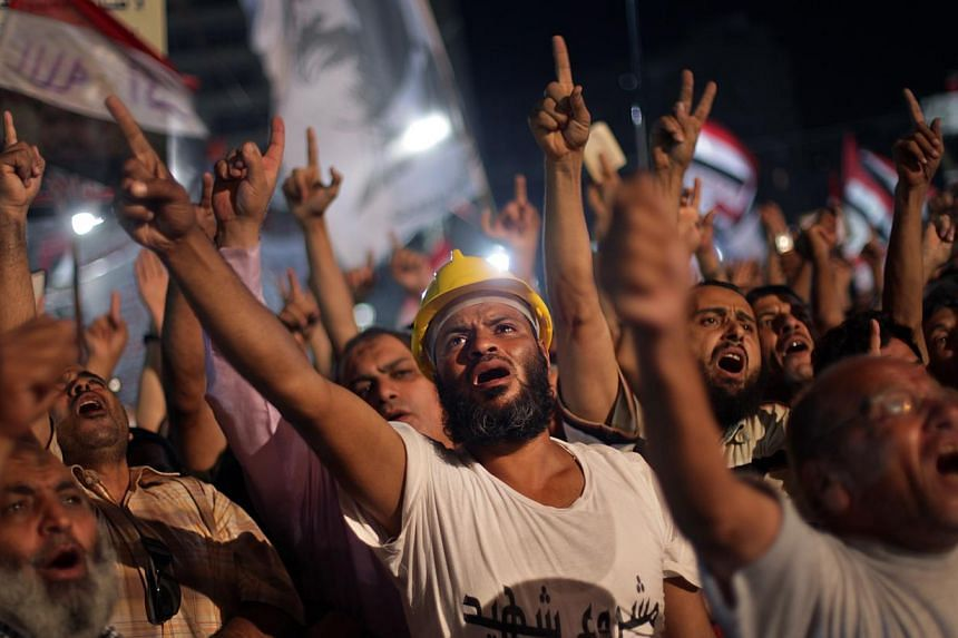 Supporters of Egypt's ousted president Mohamed Mursi chant slogans during a protest outside Rabaah al-Adawiya mosque, where they have installed a camp and hold daily rallies at Nasr City, in Cairo, Egypt on Wednesday, July 31, 2013. Egypt's interior