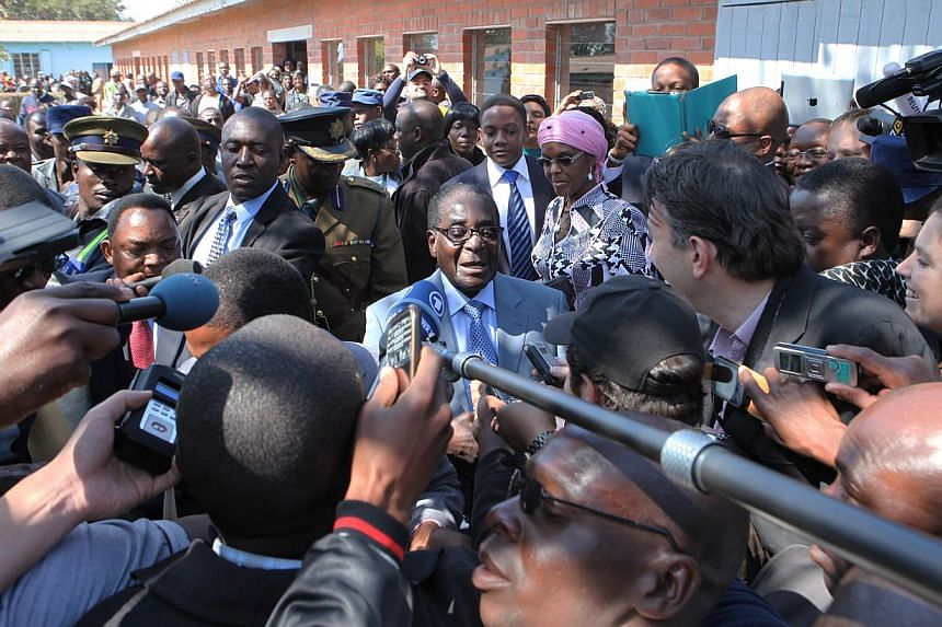 Zimbabwean President Robert Mugabe (centre) talks to the press after casting his vote in Harare on Wednesday, July 31, 2013. Mr Mugabe's party claimed a landslide election victory on Thursday, Aug 1, 2013, that would secure another five years in powe