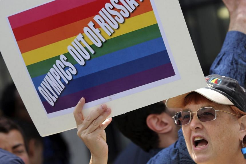 A gay rights activist chant slogans during a demonstration in front of the Russian consulate in New York, Wednesday, July 31, 2013. Demonstrators poured vodka down the drains of New York on Wednesday in protest over new Russian laws that have be
