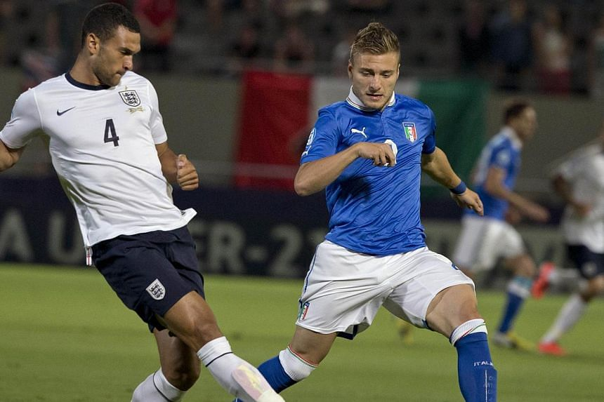 Steven Caulker (left) challenges Italy's forward Ciro Immobile during the 2013 Uefa U-21 Championship group A football match between England and Italy at Bloomfield Stadium in Tel Aviv on June 5, 2013. -- FILE PHOTO: AFP
