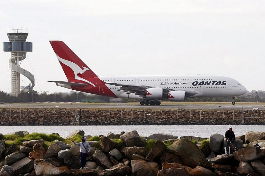 A Qantas plane takes off from Kingsford Smith International airport in Sydney on June 27, 2013.Dozens of people were rushed off a Qantas flight for medical treatment in Sydney on Thursday, Aug 1, 2013, after a stomach bug struck mid-journey, tr