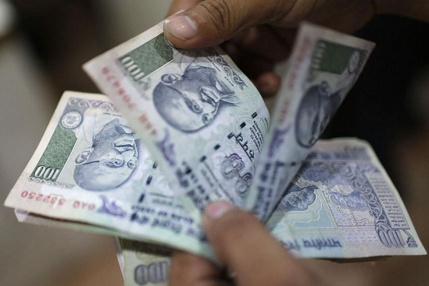 """An employee counts Indian rupee currency notes inside a private money exchange office in New Delhi on July 5, 2013. India on Wednesday stepped up its battle to halt the rupee's plunge, proposing to raise funds abroad through """"quasi-sovereign"""" bond is"""