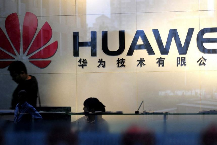 """Staff and visitors walk pass the lobby at Huawei Technologies in Wuhan, central China's Hubei province on Oct 8, 2012. Huawei has hit back at allegations by a former CIA chief that the company spies for Beijing, labelling them """"defamatory"""" and """"basel"""