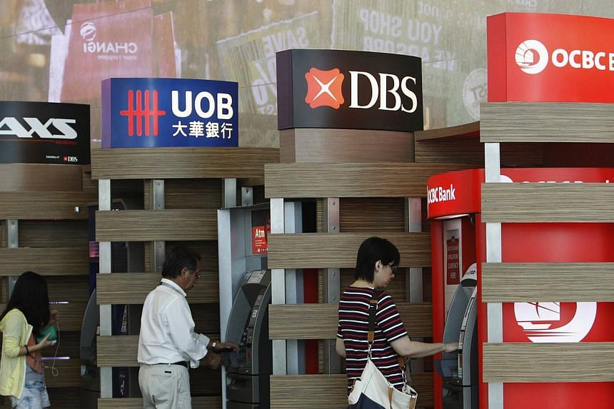 People withdraw money from United Overseas Bank (UOB), Development Bank of Singapore (DBS) and Oversea-Chinese Banking Corporation (OCBC) automated tellers in Singapore on May 17, 2013. Shares in OCBC fell after worse-than-expected quarterly results,