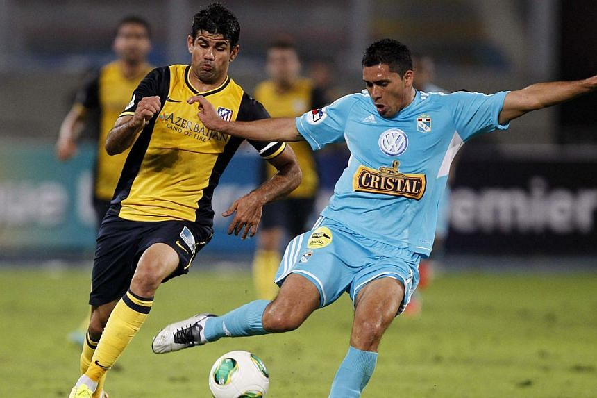 Diego Costa (left) of Spain's Atletico Madrid fights for the ball with Irvin Avila of Peru's Sporting Cristal during their Copa Euroamericana soccer match in Lima on July 31, 2013. Liverpool have submitted a £21.8million (S$42.2 million euros) bid f