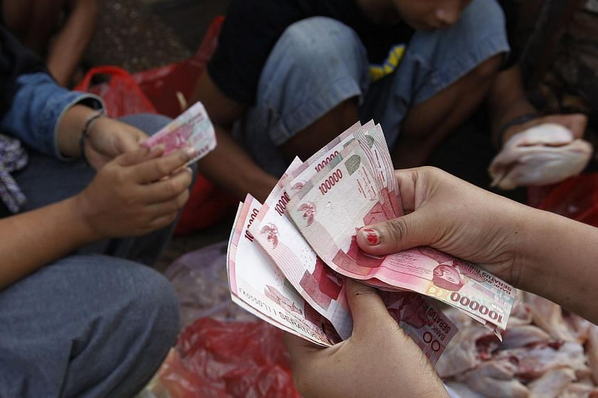 A vendor receives cash from her customer at a street market in Jakarta on July 1, 2013. -- FILE PHOTO: REUTERS