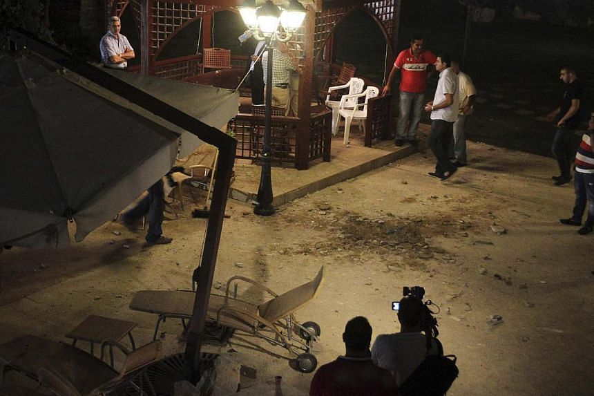 Journalists and civilians inspect the site of a private residence which was hit by a rocket in Baabda, east of Beirut, on Aug 1, 2013. -- PHOTO: REUTERS