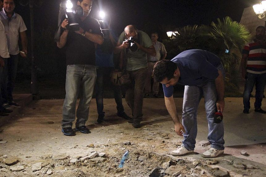 Journalists inspect the site of a private residence which was hit by a rocket in Baabda, east of Beirut on Aug 1, 2013. -- PHOTO: REUTERS