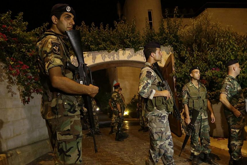 Lebanese army soldiers stand guard at the entrance to a villa where a rocket attack few metres away from one of the entrances to the Lebanese presidential palace, in Fayadiyyeh area, eastern Beirut, Lebanon, early on Friday, Aug 2, 2013. -- PHOTO: AP