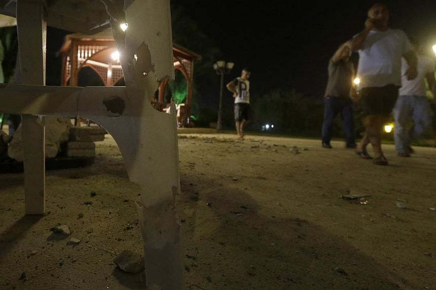 Lebanese residents walk at the scene where a rocket attacked a villa few metres away from one of the entrances to the Lebanese presidential palace, in Fayadiyyeh area, eastern Beirut, Lebanon, early on Friday, Aug 2, 2013. -- PHOTO: AP