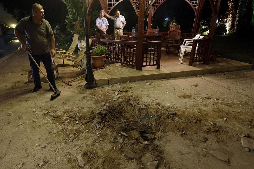 A Lebanese man (left), cleans next to a crater that left by a rocket attack at a villa few metres away from one of the entrances to the Lebanese presidential palace, in Fayadiyyeh area, eastern Beirut, Lebanon, early on Friday, Aug 2, 2013. -- PHOTO: