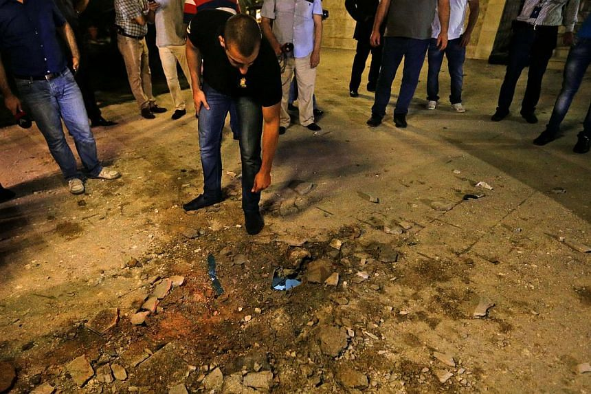A Lebanese man looks at a small crater left by a rocket attack at a villa few metres away from one of the entrances to the Lebanese presidential palace, in Fayadiyyeh area, eastern Beirut, Lebanon, early on Friday, Aug 2, 2013. -- PHOTO: AP