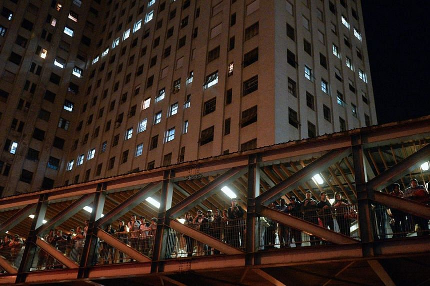 People look at demonstrator staging a protest against Sao Paulo's Governor Geraldo Alckmin and in solidarity with Rio de Janeiro's protesters seeking the impeachment of Governor Sergio Cabral accused of corruption and arrogance, in front of the City