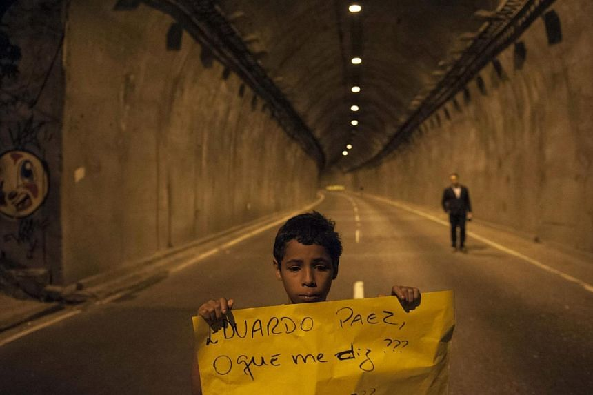 """A youth holds up a sign that reads in Portuguese """"Eduardo Paes, what do you say? Until when?,"""" referring to the mayor of Rio de Janeiro, in front of a tunnel blocked during a protest by people pressing for clarifications on missing persons, including"""