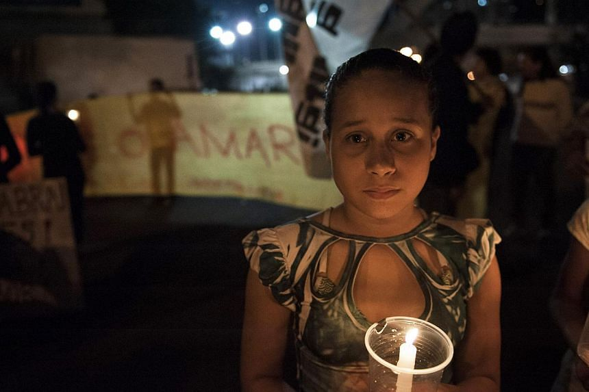 A girl holds a candle during a protest by people pressing for clarifications on missing persons including a bricklayer who recently disappeared, in Rio de Janeiro, Brazil, on Thursday, Aug 1, 2013. -- PHOTO: AP