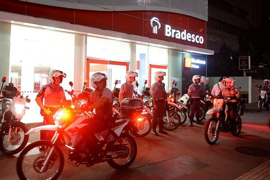 Policemen stand guard outside a bank during a demo against the disappearance of 42-year-old construction worker Amarildo de Souza who has been missing for two weeks after he was picked up by police at Rio de Janeiro's Rocinha shantytown in Sao Paulo,