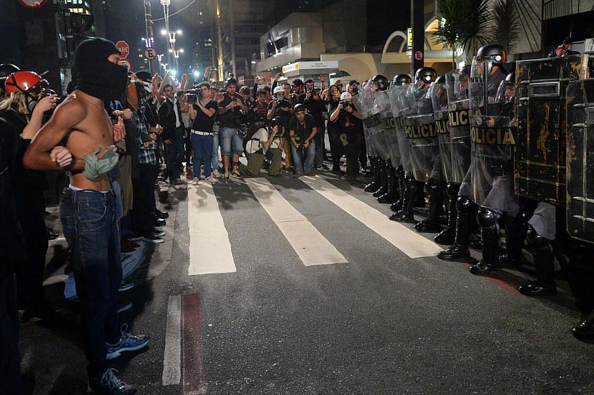 Protesters prepare to confront the police during a demo against the disappearance of 42-year-old construction worker Amarildo de Souza who has been missing for two weeks after he was picked up by police at Rio de Janeiro's Rocinha shantytown, in Sao