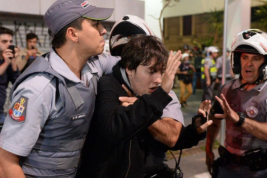A protester is detained during a demo against the disappearance of 42-year-old construction worker Amarildo de Souza, who has been missing for two weeks after he was picked up by police at Rio de Janeiro's Rocinha shantytown, in Sao Paulo, Brazil on