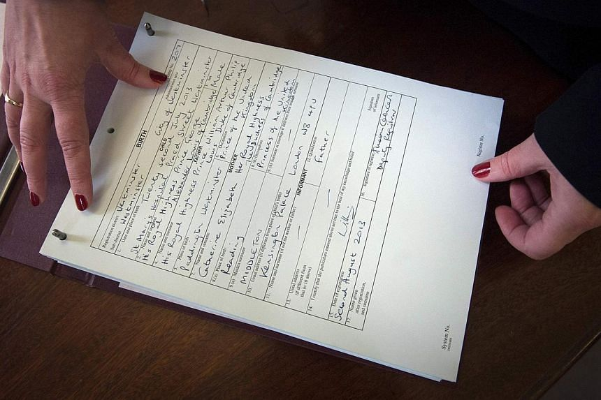 Westminster city council registrar Alison Cathcart holds a copy of the birth register of Prince George of Cambridge at Westminster Register Office in London on Friday, Aug 2, 2013. Britain's Prince William and his wife Kate on Friday registered the b