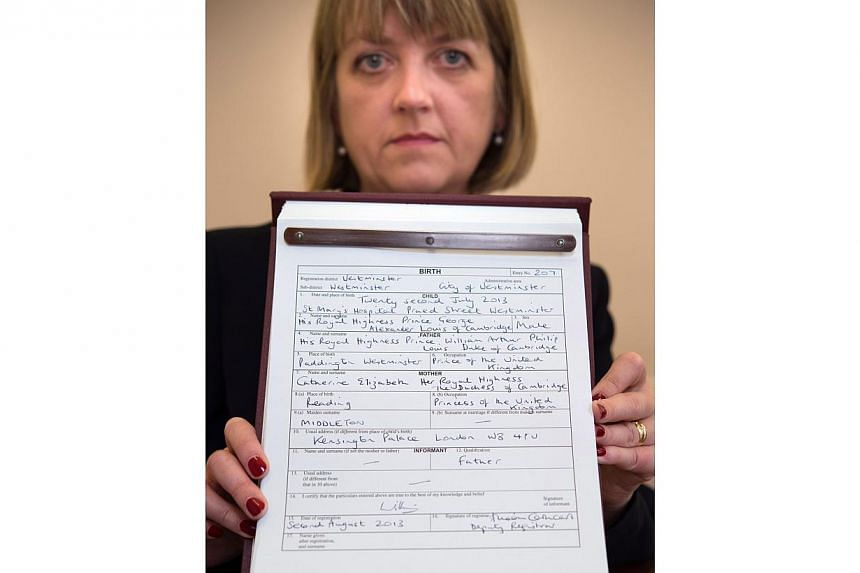 Westminster City Council registrar Alison Cathcart holds a copy of the birth register for Britain's Prince George of Cambridge, which was signed by his father, the Duke of Cambridge, at Kensington Palace in London on Friday, Aug 2, 2013. The register