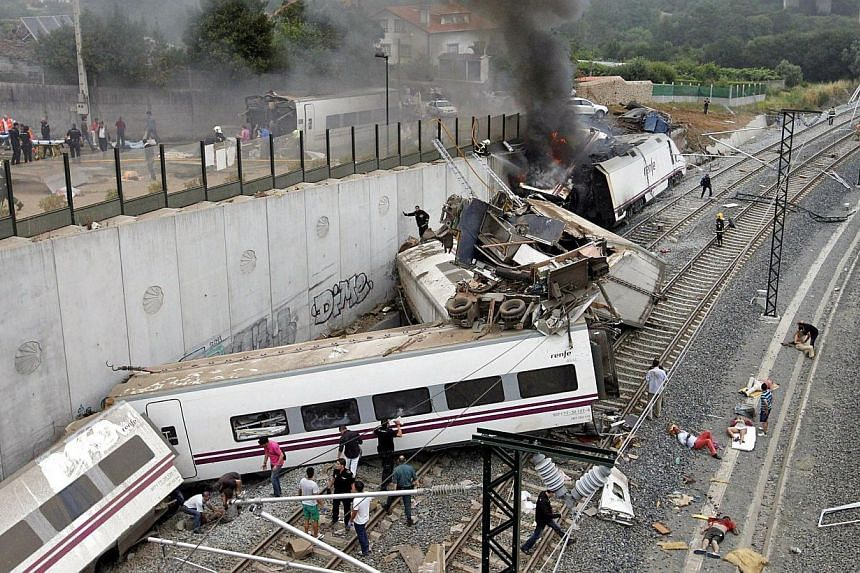 Emergency personnel respond to the scene of a train derailment in Santiago de Compostela, Spain on Wednesday, July 24, 2013. A Spanish train was hurtling around a curve at 179kmh, more than twice the speed limit, when it leapt off the tracks in a dis