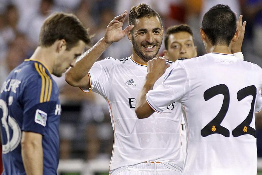 Real Madrid's Karim Benzema (centre) celebrates with teammate Angel Di Maria after his goal against Los Angeles Galaxy during their International Champions Cup football match in Phoenix, Arizona on Thursday, Aug 1, 2013. Benzema scored twice in the s