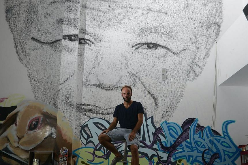 Shanghai-based 34 year-old Belgian artist Phil Akashi sits in front of his portrait of South African peace icon and former boxer Nelson Mandela, which he forged by pounding the wall 27,000 times with a boxing glove which bore the Chinese character fo