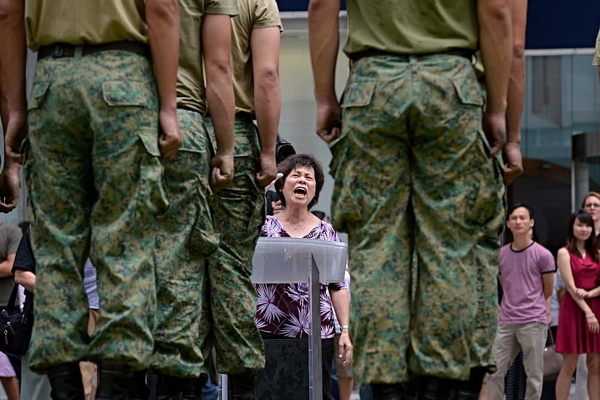 Mdm Chan Jin Peng, 66, a tea lady, delivers drill commandsto a squad of what appeared to be NS men. -- ST PHOTO: NURIA LING