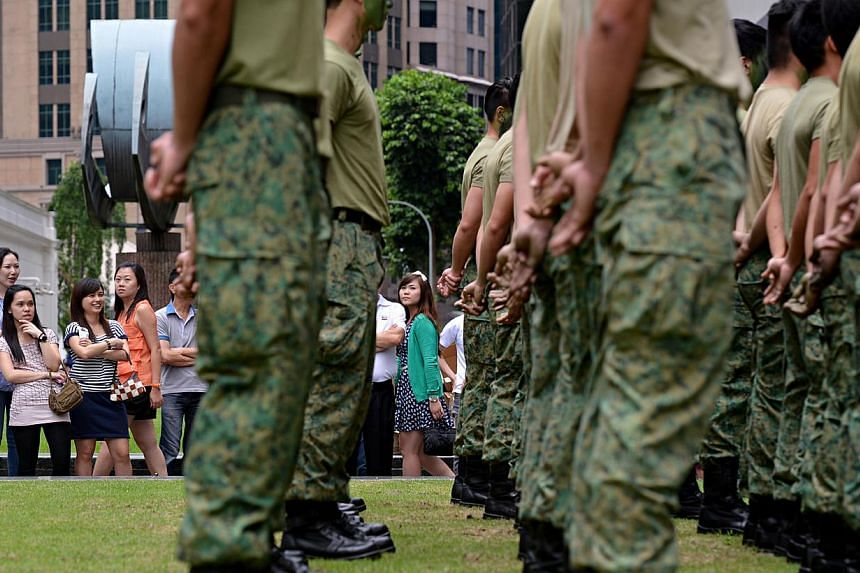 Curious onlookers gather around a squad of what appeared to be NS men who stood in formation in the heart of Raffles Place during lunch hour. -- ST PHOTO: NURIA LING