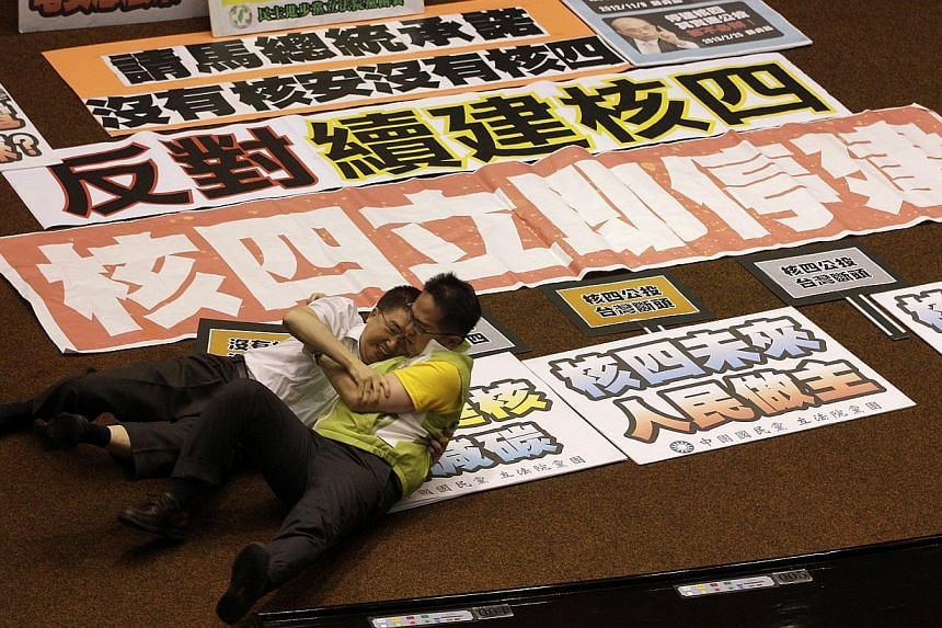 Legislator Lin Hung-chih (left) from the ruling Nationalist Party (KMT) scuffles with legislator Chiu Chih-wei from the opposition Democratic Progressive Party (DPP) at the Legislative Yuan in Taipei on Friday, Aug 2, 2013. See more pictures from aro