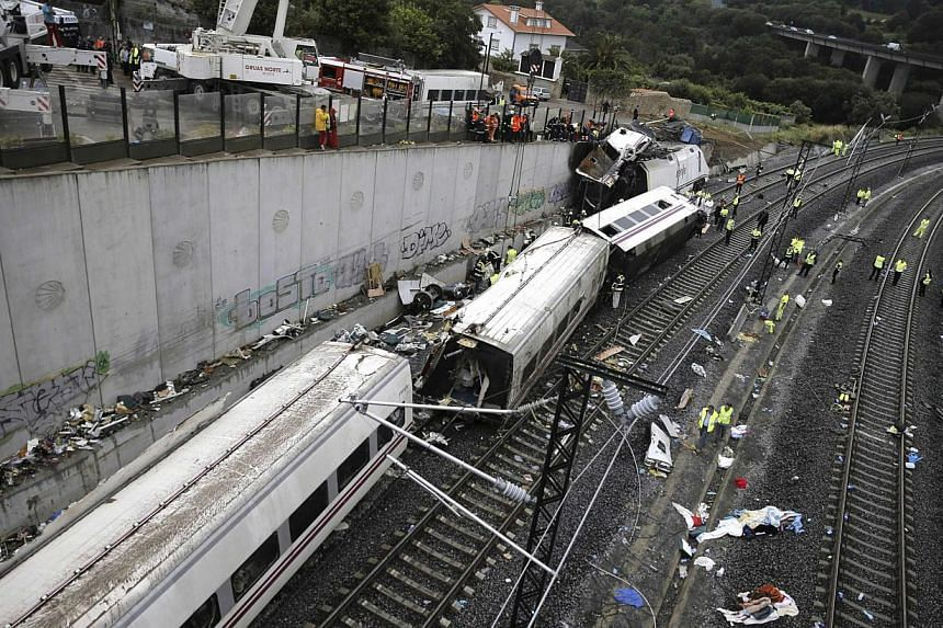 Rescue workers stand amongst the wreckage of a train crash near Santiago de Compostela, north-western Spain, on Thursday, July 25, 2013. A conductor said on Friday, Aug 2, 2013, he was not to blame for a Spanish train derailment that killed 79 people