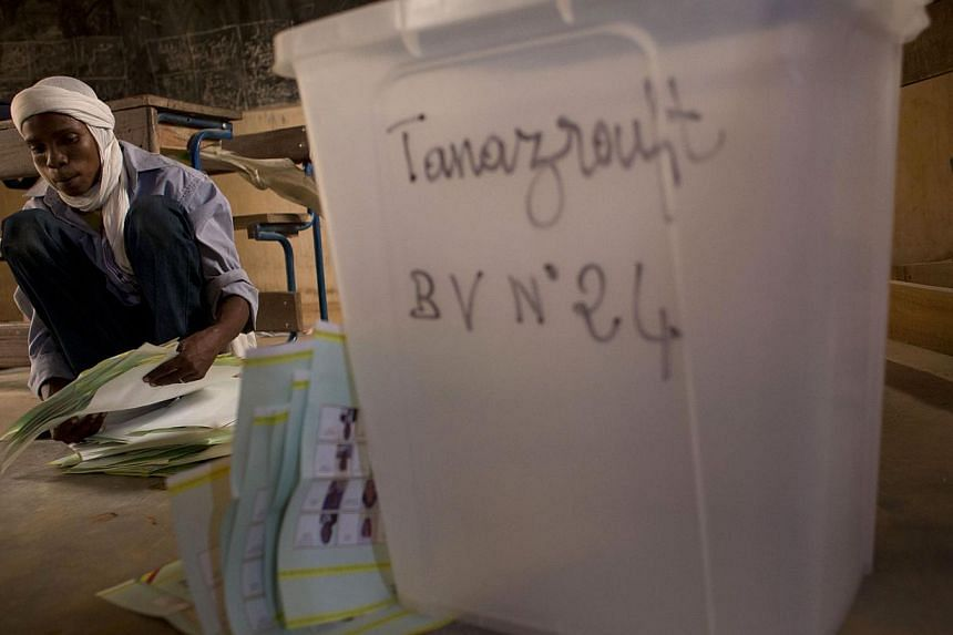 Election workers count votes at a station that reported an 88 per cent turnout, with voters filling in the registration rolls with pages of remarkably consistent signatures and thumbprints in Kidal, Mali on Sunday, July 28, 2013. Mali's presidential