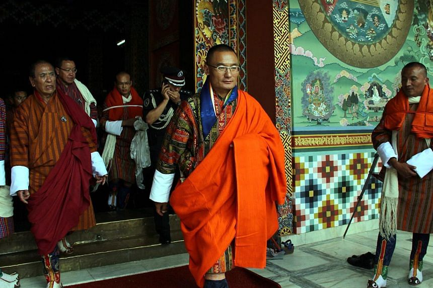 """President of the People's Democratic Party (PDP), Tshering Tobgay (centre), looks on as he walks through a hall before his appointment ceremony as Prime Minister in Thimpu on July 27, 2013. Bhutan's pursuit of """"Gross National Happiness"""" has brought i"""