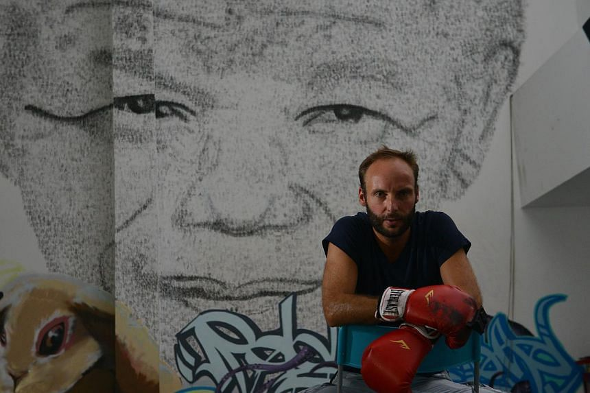 """Shanghai-based Belgian artist Phil Akashi, 34, sitting in front of his portrait of South African peace icon and former boxer Nelson Mandela, which he forged by pounding the wall 27,000 times with a boxing glove which bore the Chinese character for """"f"""