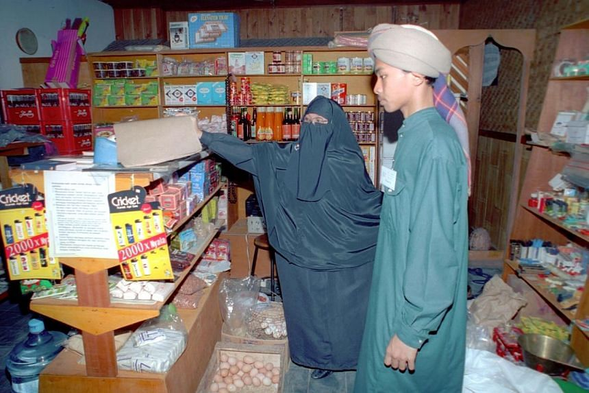 A burqa-clad Indonesian woman and an Indonesian man in turban shopping at a minimart in Depok, outside Jakarta. -- PHOTO:TEMPO/Hidayat SG