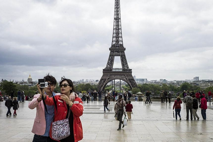 Tourists take picture of the Eiffel Tower, on Trocadero Square, on May 14, 2013 in Paris. -- PHOTO: AFP