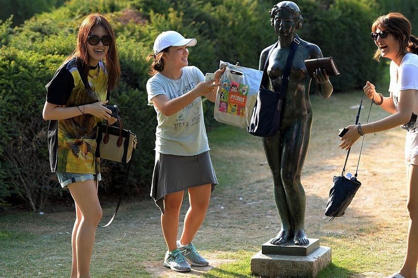 Asian tourists pose by a sculpture by Aristide Maillol in the Tulieries Gardens in Paris on July 18, 2013. -- PHOTO: AFP
