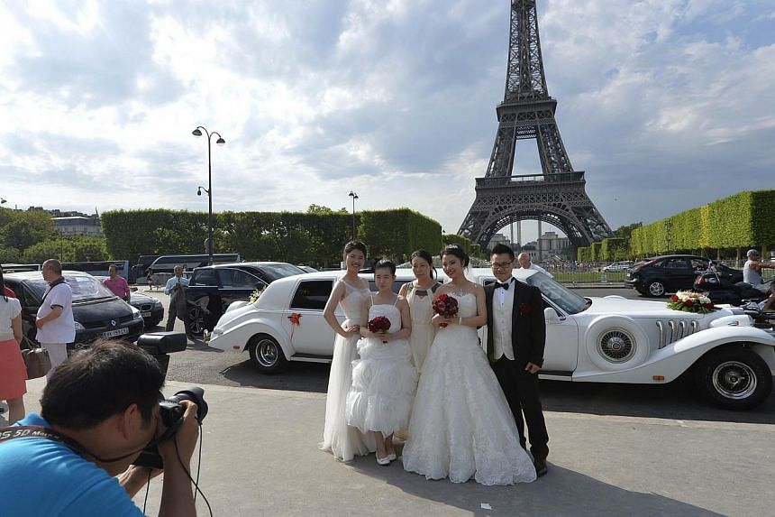 An Asian couple posed with their wedding in front of the Eiffel Tower on July 27, 2013 in Paris. -- PHOTO: AFP