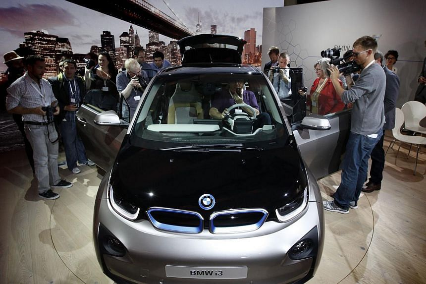 Members of the media inspect the new BMW i3 all-electric car at an unveiling event for the vehicle in New York on July 29, 2013. -- PHOTO: REUTERS