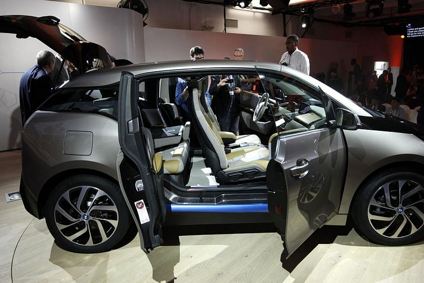 Members of the media inspect the new BMW i3 all-electric car at an unveiling event in New York, on July 29, 2013. -- PHOTO: REUTERS