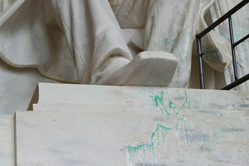 Green paint is seen on the statue of Abraham Lincoln on July 30, 2013 at the Lincoln Memorial in Washington, DC.A Chinese national charged with splattering green paint inside Washington's National Cathedral was ordered on Friday to remain in a
